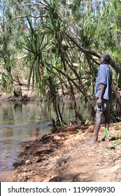 Arnhem Land, Northern Territory, Australia - August 2010: Aboriginal man wearing blue work shirt and shorts looking out at river crossing