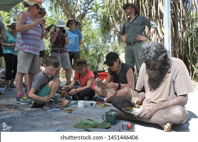 ARNHEM LAND, NT - JULY 08 2019:Aboriginal artist dot painting workshop with tourist.Aboriginal artists abstract their paint into dots to conceal sacred designs which used in cultural ceremonies.