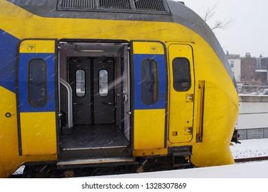 Arnhem, Netherlands - January 22, 2019: Train waiting at platform, with open doors during snowfall, at station Arnhem