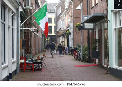 ARNHEM, NETHERLANDS - MARCH 22, 2019: Ancient street in the touristic center of Arnhem with some passers-by and pedestrians