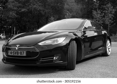 Arnhem, The Netherlands - May 17, 2015: Black Electric Tesla Motors Model S parked on a parking lot (black white) . Tesla Motors is an American automotive and energy storage company.