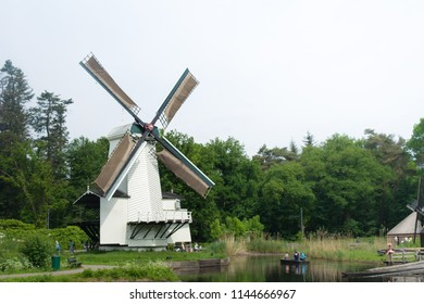 Arnhem, Netherlands - May 2018: white wind mills close to a lake at Arnhem open air and national heritage museum.