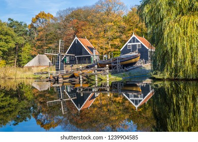 Arnhem, Netherlands - November, 04, 2018: Historic Dutch scene with an old shipyard, wooden barn and water windmill in the open air museum in Arnhem in the Netherlands