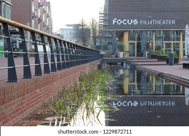 "ARNHEM, NETHERLANDS - NOVEMBER 14, 2018: Movie theater ""Focus Filmtheater"" with reflection of this building in the new stream ""Sint Jansbeek"" near to the Audrey Hepburn square"