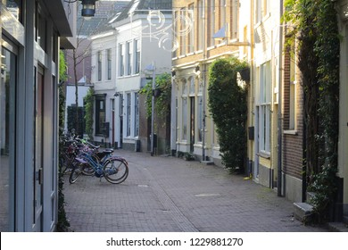 "ARNHEM, NETHERLANDS - NOVEMBER 14, 2018: ""Wielakkerstraat"", old Dutch pittoresque street in the center of Arnhem, with old houses made of bricks and many bikes parked on the street"