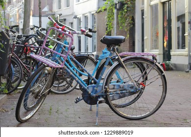 ARNHEM, NETHERLANDS - NOVEMBER 14, 2018: Dutch bicycle with an luggage carrier above the front wheel, the bikes are parked in an ancient street in the center of Arnhem