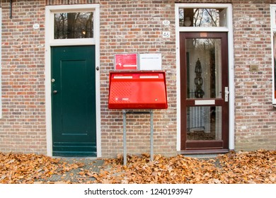 """ARNHEM, NETHERLANDS - NOVEMBER 23, 2018: Old red Dutch mailbox of company that used to be called """"TPG Post"""" to send letter and postcards at Open air museum in Arnhem"""