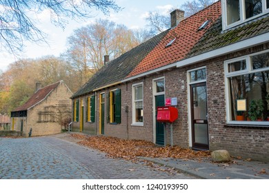 ARNHEM, NETHERLANDS - NOVEMBER 23, 2018: Typical Dutch street with old red mailbox and different color roofs on Open air museum in Arnhem