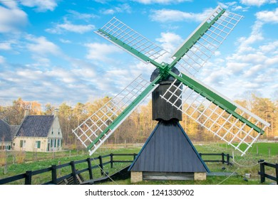 ARNHEM, NETHERLANDS - NOVEMBER 23, 2018: Green ground windmill with typical traditional Dutch architecture in the background in the open air museum in Arnhem, Netherlands on a day in the fall