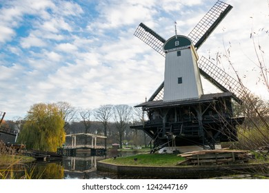 ARNHEM, NETHERLANDS - NOVEMBER 23, 2018: Typical Dutch windmill with a double drawbridge in the background in the open air museum in Arnhem, Netherlands on a sunny day in the fall