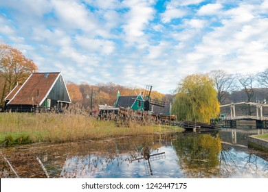 ARNHEM, NETHERLANDS - NOVEMBER 23, 2018: Typical Dutch landscape with a windmill and a drawbridge in the background in the open air museum in Arnhem, Netherlands on a sunny day in the fall
