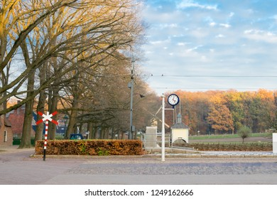 ARNHEM, NETHERLANDS - NOVEMBER 23, 2018: Railroad crossing with typical Dutch station clock and a windmill on the background at the open air museum in Arnhem