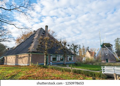 """ARNHEM, NETHERLANDS - NOVEMBER 23, 2018: Dutch farmhouse a place called """"Zuid-Scharwoude"""", a square shaped farm with a windmill at the open air museum in Arnhem"""