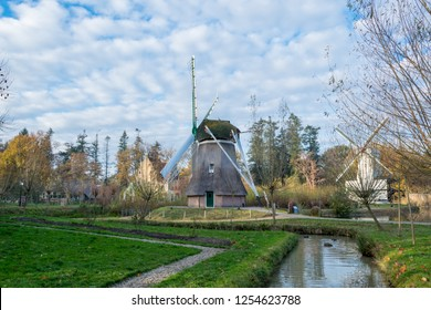 ARNHEM, NETHERLANDS - NOVEMBER 23, 2018: Two old windmills with a small canal in the Dutch open air museum in Arnhem, Netherlands