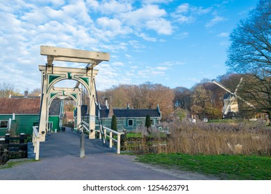 ARNHEM, NETHERLANDS - NOVEMBER 23, 2018: Double drawbridge with typical dutch houses and a windmill on the background, in Dutch open air museum in Arnhem, Netherlands