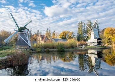 ARNHEM, NETHERLANDS - NOVEMBER 23, 2018: A typical Dutch landscape with two old windmills in the Dutch open air museum in Arnhem, Netherlands