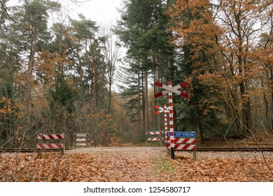 """ARNHEM, NETHERLANDS - NOVEMBER 24, 2018: Warning sign at a railroad crossing """"Let op trein"""" (Watch out train) with red and white stripes and a train track on the background"""