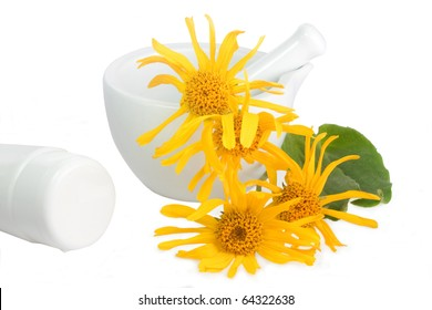 Arnica blossoms with mortar and cream tube over white