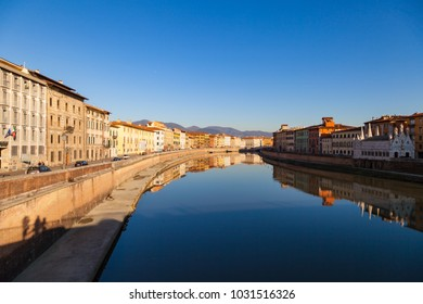 Arno river embankment with colorful old houses and Santa Maria della Spina church. Picturesque medieval town of Pisa, Tuscany, Italy.