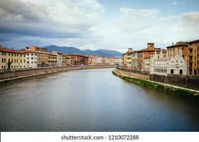 Arno river passing through Pisa City in Italy with Santa Maria della Spina church