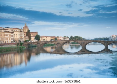 Arno River with reflections of arched bridge, domed church and riverside apartments