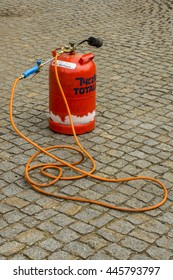 ARNSDORF, GERMANY - JUNE 10 2016: supplied tool for weeding. Gas bottle with burner is on granite paving