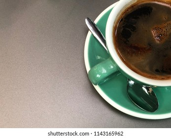 The aroma americano coffee in a green ceramic cup with white border. This cup of coffee also show smoke on the top of it. Well, this cup stand on a nice gun metal gray color table.