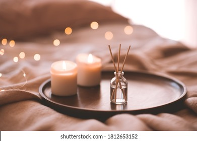 Aroma bamboo sticks in bottle with scented liquid with candles staying on wooden tray in bed closeup.  - Shutterstock ID 1812653152