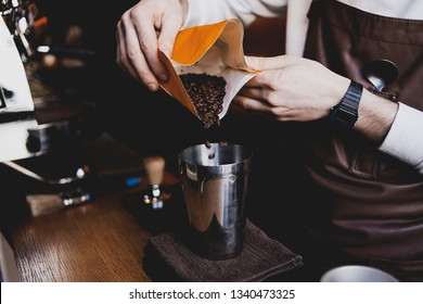 Aroma coffee beans in local coffee shop. Barista making coffee drink for client. Professional and knowledge man in his sphere. Interesting process of preparing coffee
