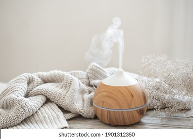 Aroma composition with a modern aroma oil diffuser on a wooden surface with a knitted element and a sprig of dried flowers. - Shutterstock ID 1901312350