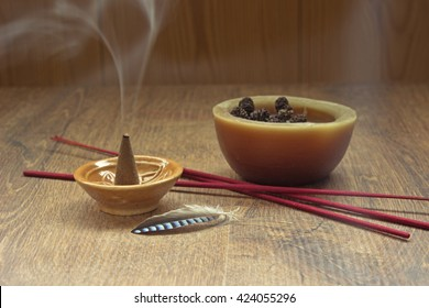 Aroma cone in a stand with the feather and some aroma sticks. Smoke incense cone in a ceramic stand. Aromatherapy theme background.