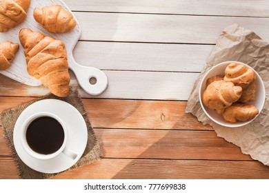 aroma cup of coffee with sweet croissant on a wooden table, european breakfast at morning, top view