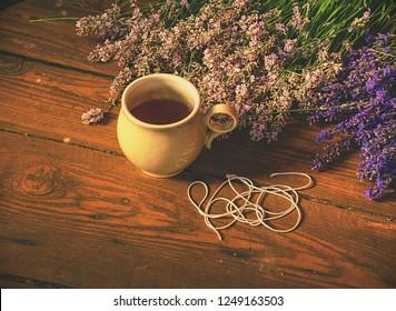 Aroma designer  workplace. Girl prepar harvested lavander stalks for drying. Rustic wooden tble with cup of herbal tea