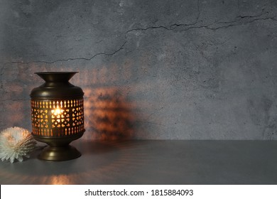 aroma essential oil brass burner is put on the grey table with a candle inside near a white flower on the background of crack cement wall in the luxurious day spa resort hotel Thailand during summer