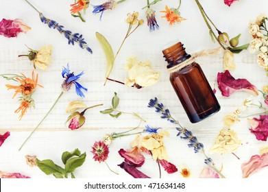 Aroma essential oil. Top view dropper bottle among colourful dried flowers, medicinal herbs  variety, scattered white wooden table. Natural cosmetic and skincare, herbal miscellany