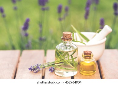 aroma essential spa oil and natural fragrance oil with lavender flower on wooden table over blurred lavender garden, image for aroma spa alternative therapy medicine and meditation concept.