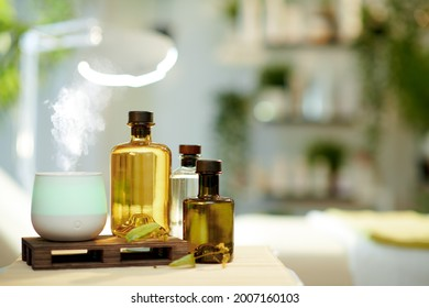 aroma lamp, essential oils and massage table in modern beauty studio.