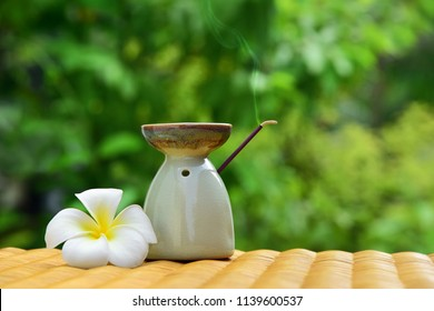 Aroma lamp with incense stick and white plumeria flower on a wicker rattan table. Zen concept. Items on green blurred background.