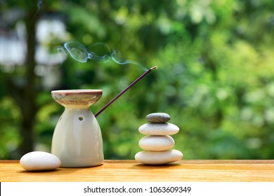 Aroma lamp with incense stick and zen stones on a wooden table. Zen concept.
