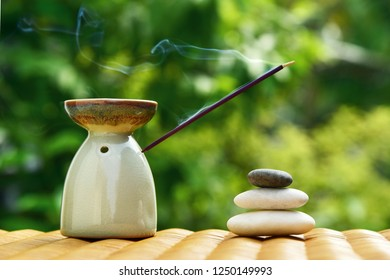 Aroma lamp with incense stick and zen stones on a wicker rattan table. Zen concept.