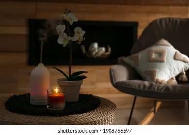 Aroma oil diffuser, burning candle and beautiful potted orchid flower on table in living room. Space for text