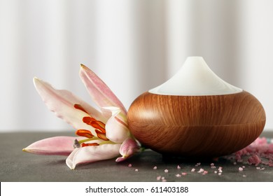 Aroma oil diffuser and flower on table