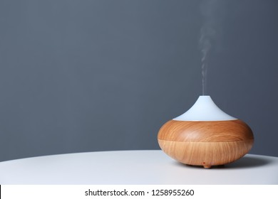 Aroma oil diffuser lamp on table against gray background. Space for text