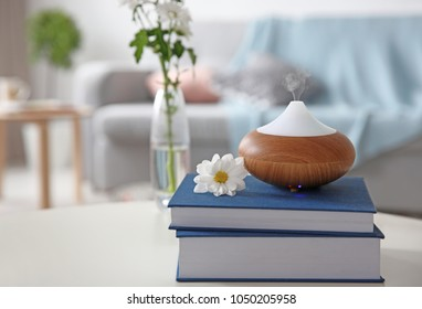 Aroma oil diffuser on stack of books against blurred background