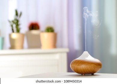 Aroma oil diffuser on table in room. Air freshener