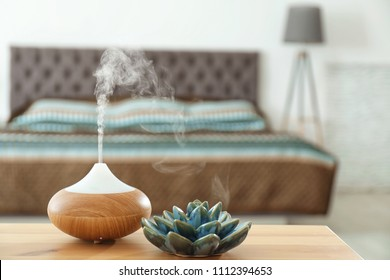 Aroma oil diffuser on table at home. Air freshener