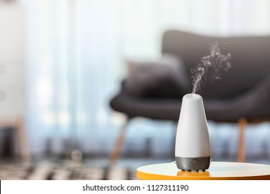 Aroma oil diffuser on table against blurred background. Air freshener