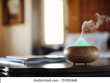Aroma oil diffuser on wooden table in room