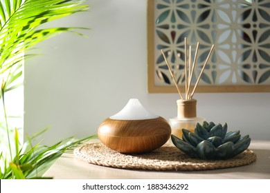 Aroma oil diffuser and reed air freshener on table in room