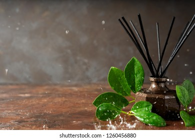 Aroma reed diffuser bottle home fragrance with rattan sticks and falling water drops, splashes on the surface with scents of freshness rain with copy space